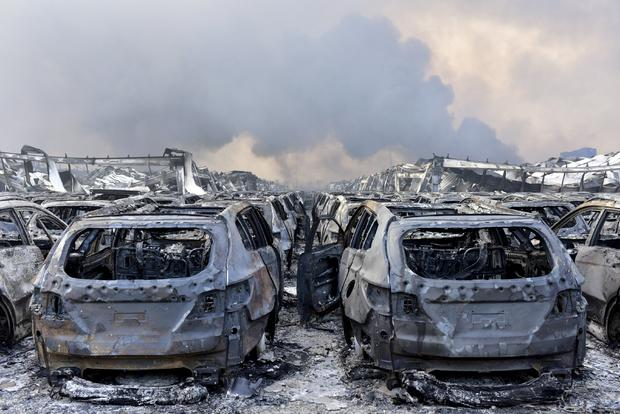 Damaged vehicles are seen as smoke rises from debris after explosions in Tianjin, China, August 13, 2015