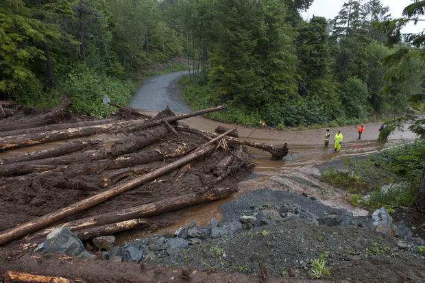 Construction workers and emergency crew members look at the damage caused by a landslide Aug. 18, 2015, in Sitka, Alaska.