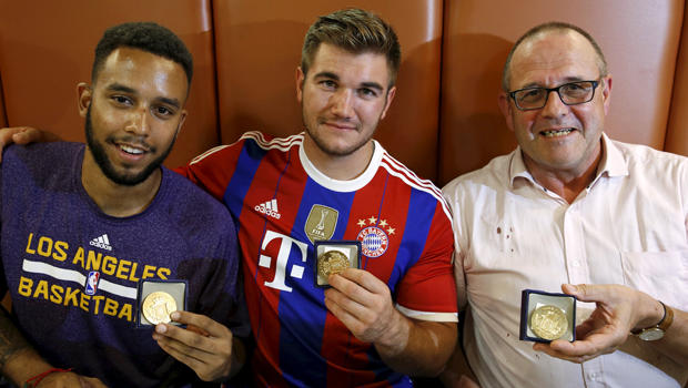 Three men who helped disarm an attacker on a train from Amsterdam to France, from left, Anthony Sadler, from Pittsburg, California, Aleck Sharlatos, from Roseburg, Oregon, and Chris Norman, a British man living in France, pose with medals they received f