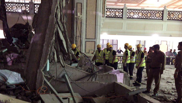 In this image released by the Saudi Interior Ministry's General Directorate of Civil Defense, Civil Defense personnel inspect the damage at the Grand Mosque in Mecca after a crane collapsed, killing dozens, Sept. 11, 2015.
