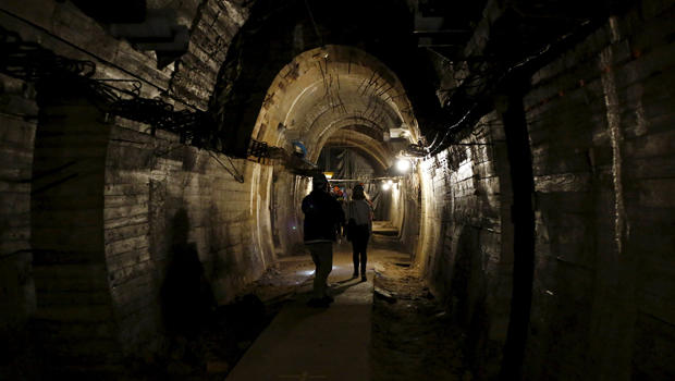 """People walk through a tunnel, which is part of the Nazi Germany """"Riese"""" construction project, under the Ksiaz castle in an area where a Nazi train is believed to be, in Walbrzych, Poland, Sept. 3, 2015."""