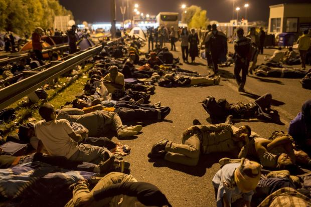 Migrants sleep on a highway in front of a barrier at the border with Hungary near the village of Horgos, Serbia