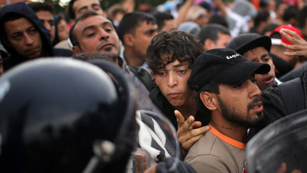 Migrants are held back by Slovenian riot police at the border in the small Croatian village of Harmica Sept. 19, 2015, in Harmica, Croatia.