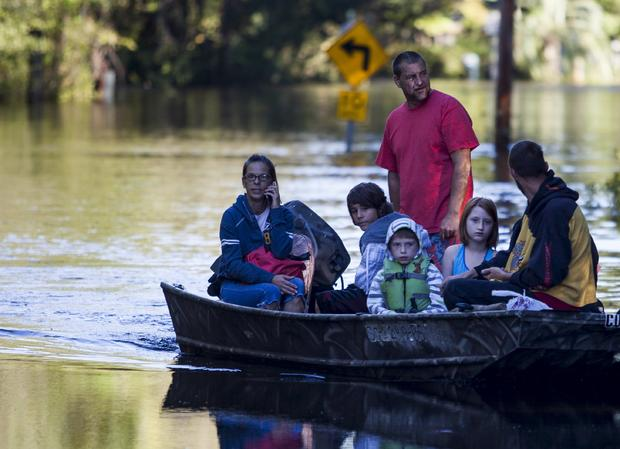 Scott Everett, standing, transports his family on a johnboat along Lee's Landing Circle in Conway, South Carolina, Oct. 7, 2015.