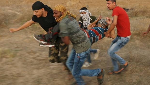 A wounded Palestinian protester is evacuated during clashes with Israeli troops near the border between Israel and Central Gaza Strip