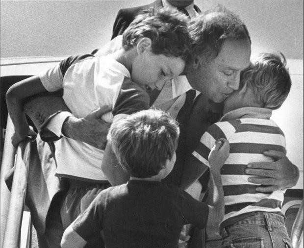 Canadian Prime Minister Pierre Trudeau greets his sons Justin (left), Sacha (right) and Michel after returning home from a foreign trip to Ottawa, in a 1983 file photo