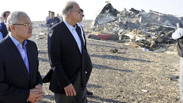 Egypt's Prime Minister Sherif Ismail, second left, and Tourism Minister Hisham Zaazou look at the remains of a Russian airliner which crashed in central Sinai near El Arish city, north Egypt, Oct. 31, 2015.