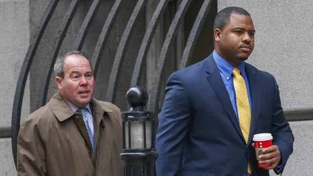 Baltimore Police Officer William Porter, right, approaches the courthouse in Baltimore, Maryland, Nov. 30, 2015. Porter is one of six Baltimore police officers charged in connection with the death of Freddie Gray.