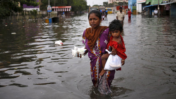 A woman carries her child and milk packets as she wades through a flooded street in Chennai, India, Dec. 5, 2015.