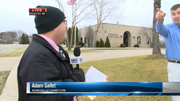 A bank employee interrupts a live news report to point out a suspected bank robber in Rochester, Minn., Dec. 15, 2015.