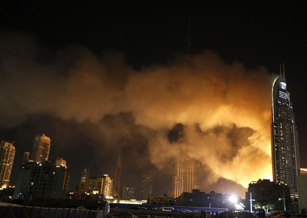 Smoke billows from the Address Downtown Hotel, after it caught on fire hours earlier, past fireworks, near the Burj Khalifa, the world's tallest tower, in Dubai
