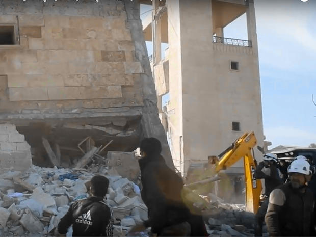 """Members of the """"White Helmets"""" Syrian rescue force and others climb over debris around a building that had been used as a makeshift clinic in Idlib province"""