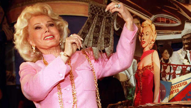 Actress Zsa Zsa Gabor holds up a beaded purse removed from a 30-year-old trunk containing possessions from actress Marilyn Monroe on April 11, 1996, at Planet Hollywood in Beverly Hills, California.