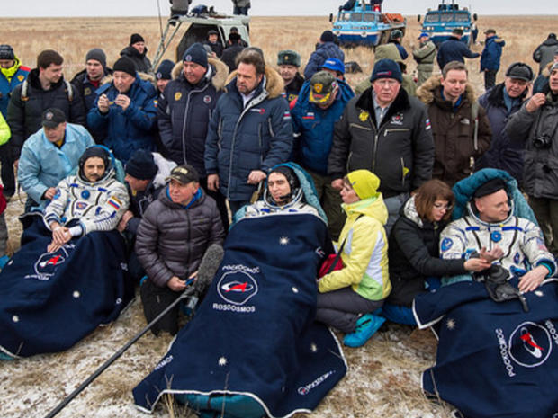 Cosmonaut Mikhail Kornienko, left, astronaut Scott Kelly, center, and spacecraft commander Sergey Volko, surrounded by ground crew members after returning to Earth, in Kazakhstan, on March 2, 2016