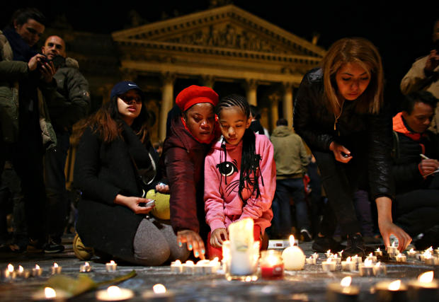 ​A young girl lights a candle at the Place de la Bourse following attacks in Brussels, Belgium, on March 22, 2016.