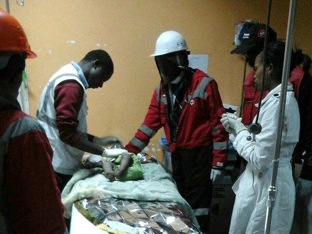 ​An image released by the Kenya Red Cross shows rescuers and medical workers caring for a 1-year-old girl rescued on May 3, 2016, from the rubble of a collapsed building in Nairobi