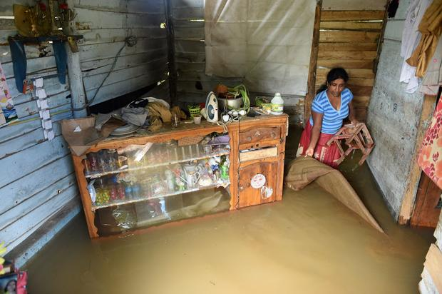 A Sri Lankan woman wades through floodwaters inside her home in Kelaniya suburb of the capital Colombo