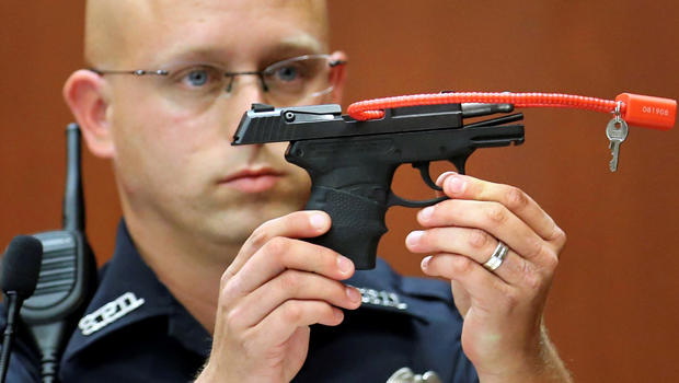 Sanford police officer Timothy Smith holds up the gun that was used to kill Trayvon Martin while testifying during George Zimmerman's murder trial in Seminole circuit court in Sanford, Florida, June 28, 2013.