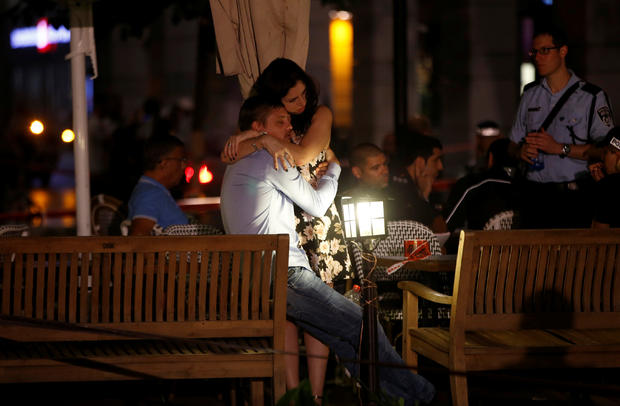 People hug each other following June 8, 2016 terror attack in Tel Aviv market