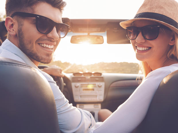 Our perfect weekend journey. Rear view of cheerful young couple looking over shoulder and smiling while sitting inside of their convertible