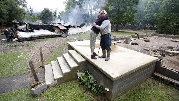 Jimmy Scott gets a hug from Anna May Watson, left, as they clean up from severe flooding in White Sulphur Springs, West Virginia, June 24, 2016.