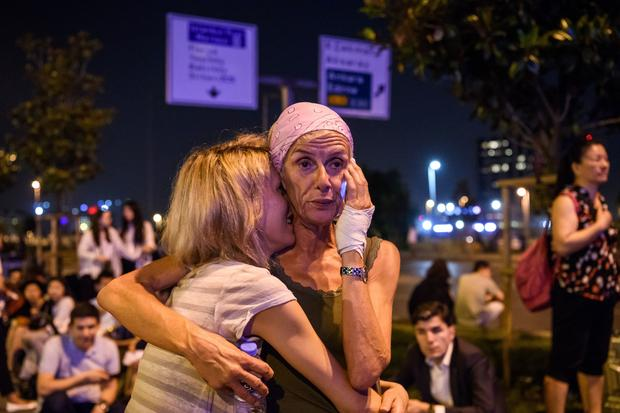 Passengers embrace outside main entrance of Ataturk Airport in Istanbul, Turkey on June 28, 2016, after blasts and gunfire left dozens dead and injured