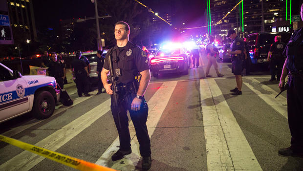 Police officers stand guard at a barricade following the sniper shooting in Dallas on July 7, 2016.
