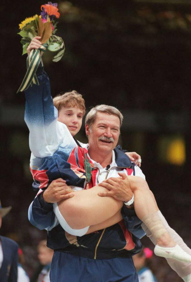 U.S. Olympic gymnastics coach Bela Karolyi carries injured gymnast Kerri Strug onto the podium after his team won the women's gold medal, July 23, 1996, in Atlanta.