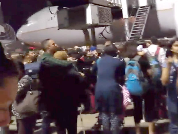 Passengers stand on a tarmac at Los Angeles International Airport late on Aug. 28, 2016, after at least one terminal was evacuated following unconfirmed reports of an active shooter in the building
