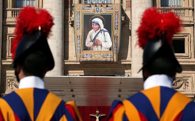Swiss Guards stand in front of a tapestry depicting Mother Teresa of Calcutta before a mass, celebrated by Pope Francis, for her canonisation in Saint Peter's Square
