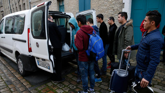 Afghani adolescent migrants place their belongins into a van as they depart the emergency shelter in Saint Omer, France, as they travel to Britain