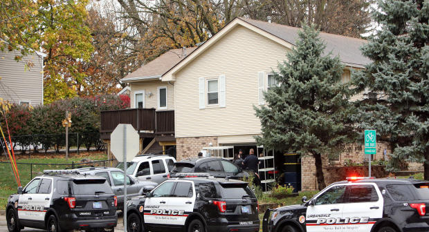 """Urbandale police officers gather outside the home of Scott Michael Greene, the suspected gunman of two police officers who were shot and killed in separate attacks described as """"ambush-style"""" in Urbandale and Des Moines, Iowa, Nov. 2, 2016."""