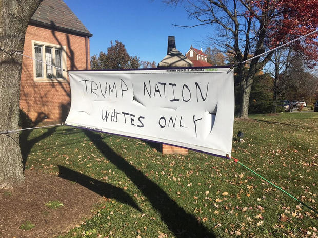 "Image of a battered plain white banner with all-caps marker writing held by four strings, two of them attached to a tree next to a brick house. Writing reads ""TRUMP NATION, WHITES ONLY"". Caption: Donald Trump's election brought about a rise in hate crimes. Photo courtesy of CBS News."