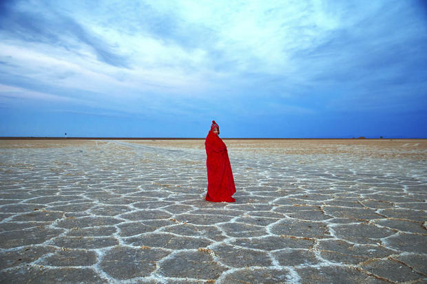 An Iranian woman covers herself with a blanket due to the cold while visiting Khour salt lake during her tour of the Mesr desert about 305 miles southeast of the capital Tehran Dec. 1, 2016. Deserts make up parts of Iran which have recently become tourist destinations for young Iranians looking for a break on their weekend. The increase in tourists to the desert has stimulated economic growth in the area.