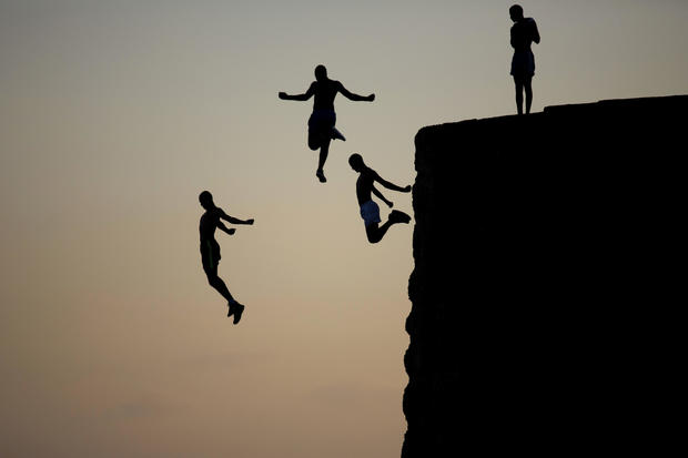 Israeli Arab boys jump into the Mediterranean Sea from the ancient wall surrounding the old city of Acre, northern Israel, Aug. 2, 2016.