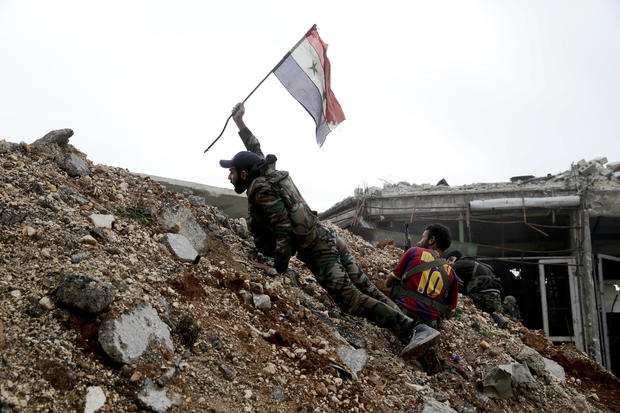 A Syrian army soldier places a Syrian national flag during a battle with rebel fighters at the Ramouseh front line, east of Aleppo, Syria, Dec. 5, 2016.