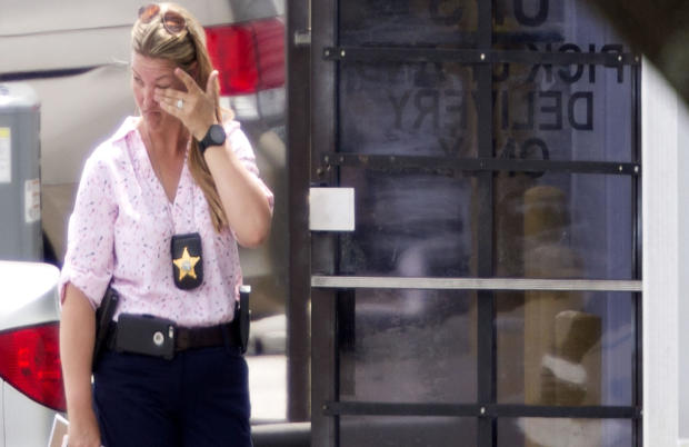 A law enforcement official wipes her eyes at the entrance to a shooting crime scene in Orlando, Florida, on June 5, 2017.