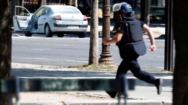 A French gendarme runs past a car on the Champs-Elysees after an incident in Paris, France, June 19, 2017.