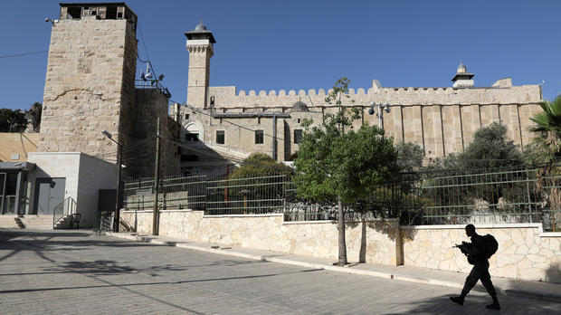 An Israeli soldier walks past Ibrahimi Mosque, which Jews call the Tomb of the Patriarchs, in the West Bank city of Hebron July 7, 2017.