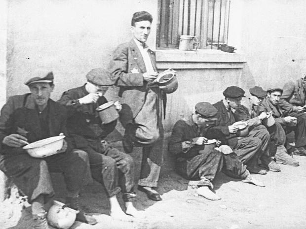 lodz-ghetto-08-group-of-men-alongside-building-eating-from-pails-henryk-ross.jpg
