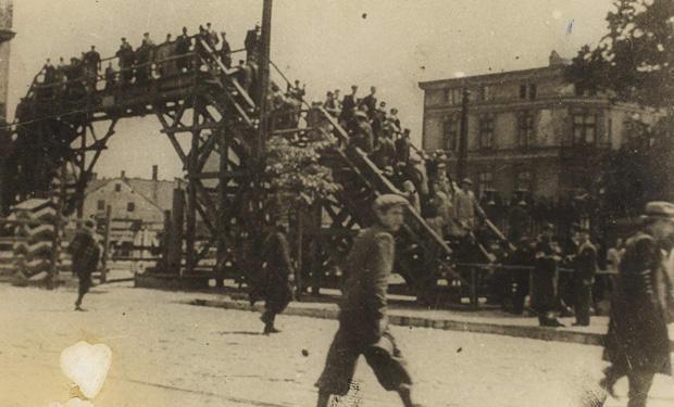lodz-ghetto-11-boy-walking-in-front-of-a-ghetto-bridge-henryk-ross.jpg