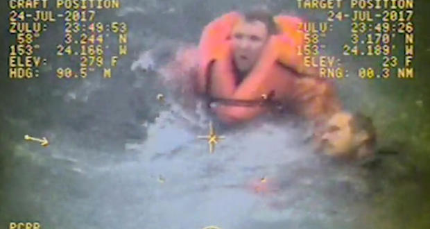The captain of the fishing vessel Grayling, left, rescues one of his crewmen after the vessel capsized in the Kupreanof Strait near Raspberry Island, Alaska, in this still image from video taken on July 24, 2017, by the Coast Guard.