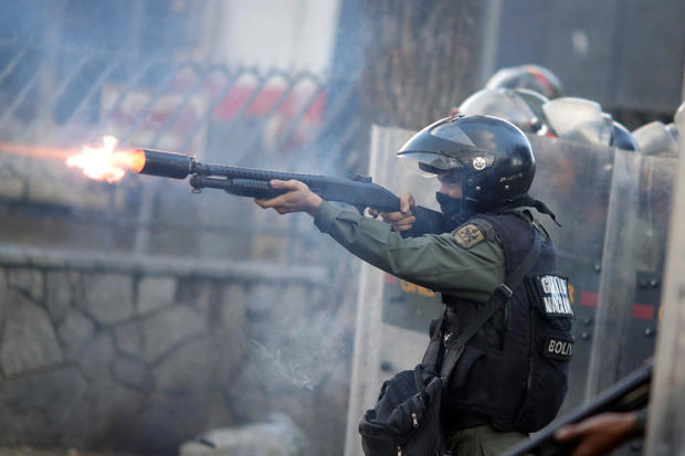 A riot security force member fires his weapon at a rally during a strike called to protest against Venezuelan President Nicolas Maduro's government in Caracas, Venezuela, July 26, 2017.