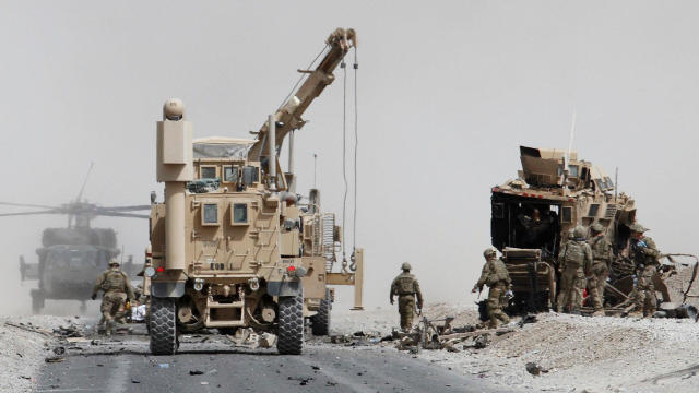 U.S. troops assess the damage to an armored NATO vehicle after a Taliban suicide attack in Kandahar province, Afghanistan, Aug. 2, 2017.