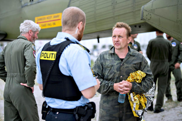 Danish submarine owner and inventor Peter Madsen, right, lands with the help of the Danish navy in Dragor Harbor south of Copenhagen, Denmark, Aug. 11, 2017.