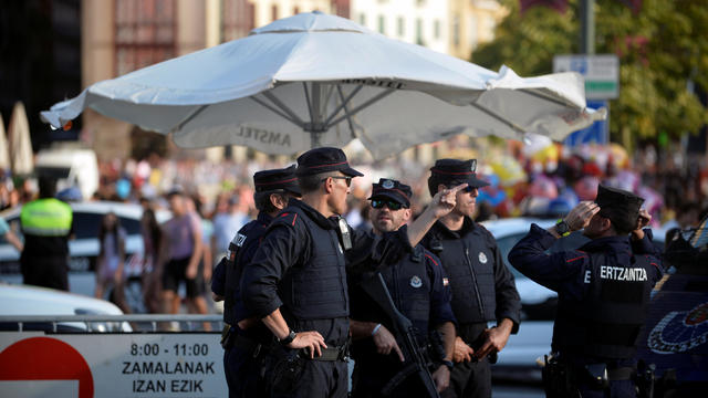 Police officers stand at a road block at the beginning of fiestas in Bilbao, after a van ran down pedestrians in Barcelona's Las Ramblas on Thursday