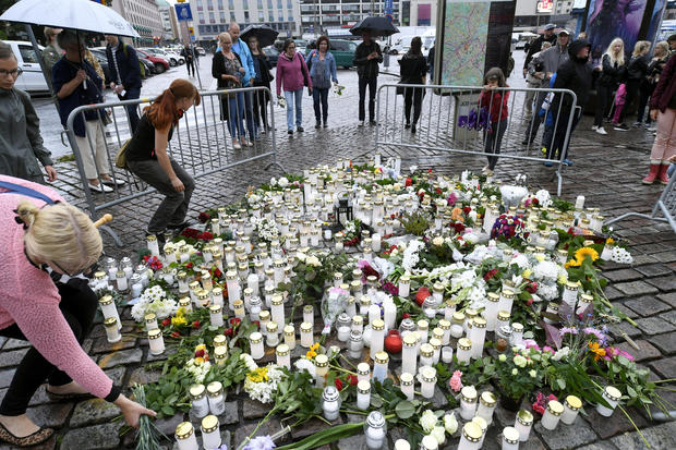 People bring memorial candles and flowers to the Turku Market Square for the victims of Friday's stabbings in Turku