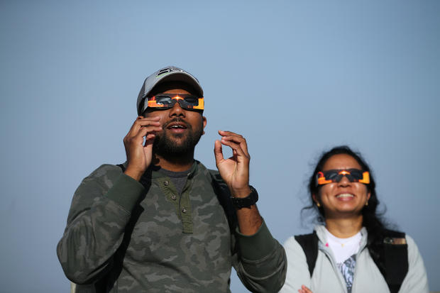 People use solar viewing glasses as the sun emerges through fog cover before the solar eclipse in Depoe Bay