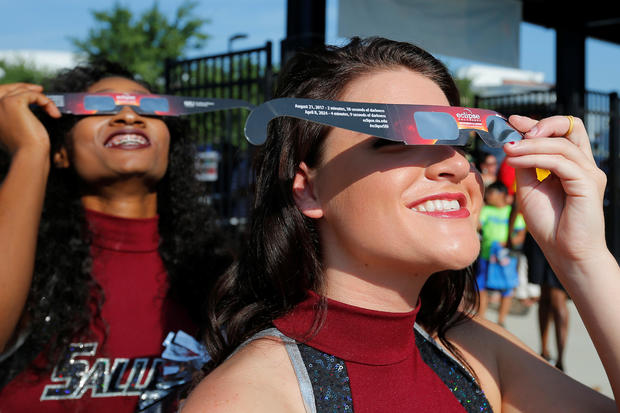 Cheerleaders use solar viewing glasses before welcoming guests to the football stadium to watch the total solar eclipse at Southern Illinois University in Carbondale