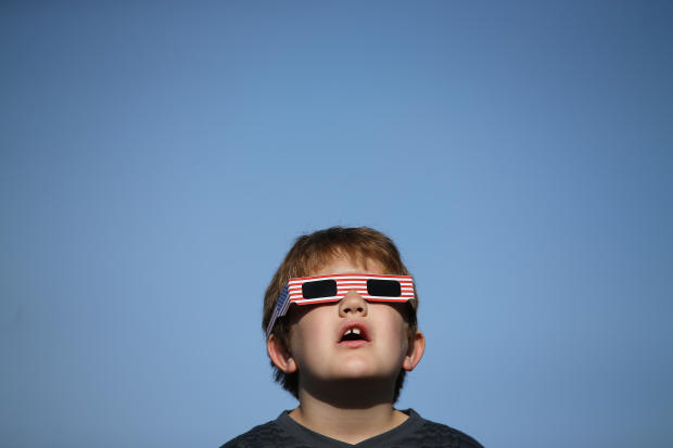 A boy uses solar viewing glasses as the sun emerges through fog cover before the solar eclipse in Depoe Bay